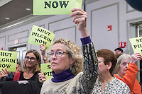 "Elizabeth Hogan, of Brewster, Mass., holds a sign reading ""Shut Pilgrim Now"" at a public hearing regarding Pilgrim Station, a nuclear power plant run by Entergy, at Hotel 1620 in Plymouth, Massachusetts, USA, on Tues., Jan. 31, 2017. Hogan is a member of the Cape Downwinders, a group of area residents opposing the continued operation of Pilgrim Station. An email from the NRC was leaked in December 2016 outlining problems with the ""safety culture"" at the plant and an ""overwhelmed"" staff. Area residents have been calling for the plant to be shut down. The green signs in the audience, reading ""Shut Pilgrim Now,"" are from a group of area residents calling for the plant's closure called Cape Downwinders."