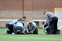 CHAPEL HILL, NC - MARCH 10: Head coach Mike Pressler of Bryant University watches as medical personnel turn over Keaton Jones #29 who was injured during a game between Bryant and North Carolina at Dorrance Field on March 10, 2020 in Chapel Hill, North Carolina.