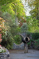 A contemporary statue in the garden, framed by a circular hole cut in the stone wall