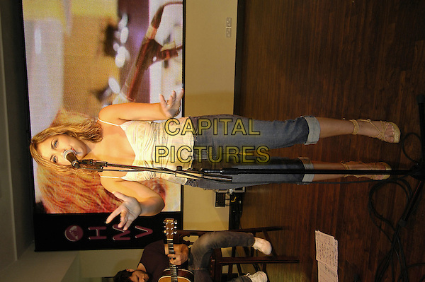 CHARLOTTE CHURCH.Performs live at HMV during a instore gig and signing session, HMV Oxford Street, London,.July 12th 2005..full length yellow striped vest top denim cropped jeans wedges wedge shoes hands.Ref: HT.www.capitalpictures.com.sales@capitalpictures.com.©Hugh Thompson/Capital Pictures