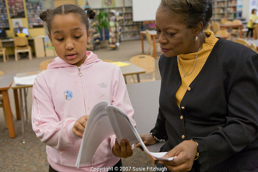 Madrona K-8 School in Seattle, WA: Ernestine Rutledge, K-5 Administrator and Head Teacher, talks to a student about her library research project.