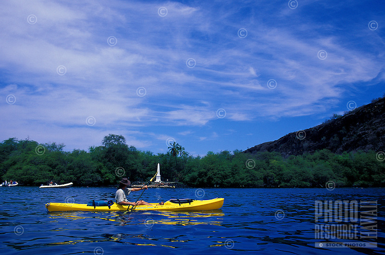 Kayaker paddles in Kealakekua Bay, with the Captain Cook Monument in the background. As of 2013 a moratorium halting all kaying in the bay has been issued by the Dept. of Land and Natural Resources. This could be revoked at anytime.