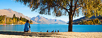 An panoramic photo of a tourist sitting enjoying the view over an autumnal Lake Wakatipu, Queenstown, South Island, New Zealand