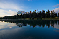 Perfect Reflection of Mount rundle in the early morning. Symmetrical reflection, blue sky and trees