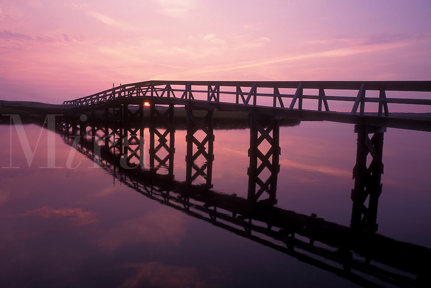 bridge, Cape Cod, Sandwich, Massachusetts, Atlantic Ocean, The sunrises over the inlet. The silhouette of the board walk reflects in the water of Cape Cod Bay.