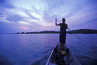 Local boy paddling dugout canoe at sunset on remote island, Philippines