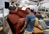 NWA Democrat-Gazette/DAVID GOTTSCHALK Ben Matthews (left) and Josh Kueh, move a chair Monday, July 8, 2019, for a customer <br /> at the Potter's House Thrift Store in Fayetteville. The non profit reduces and discounts the prices of items based on the length of time they are in inventory. Funds raised go to the ministry of Potter's House.