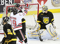 Nebraska-Omaha's Ryan Walters (19) takes a hit from Colorado College's Michael Boivin after scoring. Nebraska-Omaha defeated Colorado College 7-5 Friday night at CenturyLink Center in Omaha. (Photo by Michelle Bishop) .