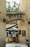 A stone archway leads into a square of trendy cafes, Montpellier, Southern France, October 7 2008