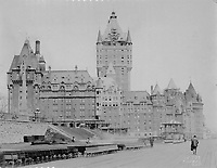 Construction work on the roof of the Chateau Frontenac, seen from the Dufferin Terrace, photograph, 1921, from the Archives of the Chateau Frontenac, Quebec City, Quebec, Canada. The Chateau Frontenac opened in 1893 and was designed by Bruce Price as a chateau style hotel for the Canadian Pacific Railway company or CPR. It was extended in 1924 by William Sutherland Maxwell. The building is now a hotel, the Fairmont Le Chateau Frontenac, and is listed as a National Historic Site of Canada. The Historic District of Old Quebec is listed as a UNESCO World Heritage Site. Copyright Archives Chateau Frontenac / Manuel Cohen
