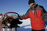 """Tuesday March 6, 2007   Nikolai resident Greg Tony pets """"Burt"""" one of Ramy Brooks' dogs  as it sits in the sled bag with teammate """"Skittles"""" at the Nikolai checkpoint on Tuesday.  Burt and Skittles were injured on the run from Rohn forcing Ramy to haul them the rest of the way and then drop them both at Nikolai."""