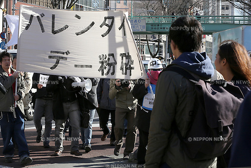 "A couple look at demonstrators take part in ""Smash Valentine's Day"" protest as they march through the streets of Shibuya district in Tokyo, Japan on February 14, 2015. The group called Kakuhidou, meaning  ""Revolutionary alliance of men whom women find unattractive"" protested that Valentine's Day  is only about marketing and making money by chocolate companies.  (Photo by Yuriko Nakao/AFLO)"