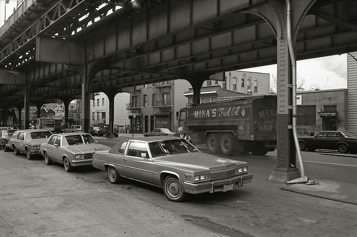 A man gets into his car as a fuel lorry passes under the El in Queens, New York City. 1989.