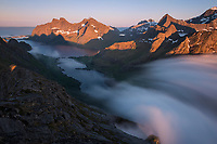 Summer fog flows over mountain pass towards Vindstad, Moskenesøy, Lofoten Islands, Norway