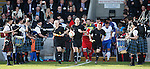 Referee Bobby Madden and officials lead the teams out past a pipe and drum guard of honour