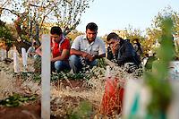 SYRIEN, 07.2014, Koreen (Provinz Idlib). Leben ohne Zentralregierung: Am Feiertag Eid al-Fitre (der Tag, der dem Ende des Ramadans folgt), besuchen Moslems traditonell am fruehen Morgen die Graeber ihrer Verwandten. Seit dem Beginn des Aufstandes gilt dies ganz besonders fuer die Friedhoefe wo Gefallene liegen. Das Schicksal schweisst die Menschen zusammen. | Life without a central government: During holy Eid al-Fitre (the day following the end of Ramadan) muslims traditonally visit their relatives' graves in the very early morning. Since the uprising started cemeteries of the martyrs are more frequented as destiny ties people together.© Timo Vogt/EST&OST
