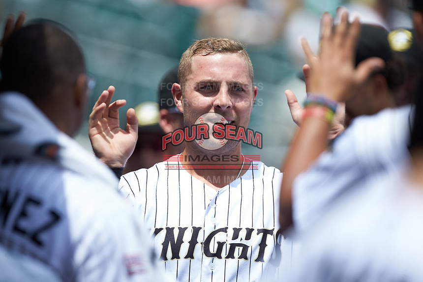 Matt Skole (12) of the Charlotte Knights is congratulated by his teammates after scoring a run against the Indianapolis Indians at BB&T BallPark on August 22, 2018 in Charlotte, North Carolina.  The Indians defeated the Knights 6-4 in 11 innings.  (Brian Westerholt/Four Seam Images)