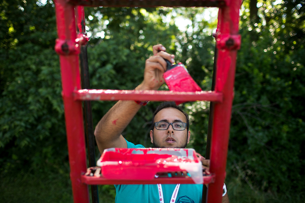 "Nick Stringfellow paints a playground slide during ""Circle the City with Service,"" the Kiwanis Circle K International's 2015 Large Scale Service Project, on Wednesday, June 24, 2015, at the Friendship Westside Center for Excellence in Indianapolis. (Photo by James Brosher)"