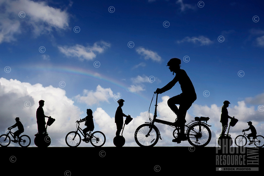 Bicyclists and Segway riders in silhouette against blue sky with rainbow.