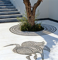 A detail of the courtyard which has inlaid pebble motifs and concentric circles around the olive trees