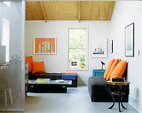 In the guest bedroom bright orange cushions add vibrant notes to the black sofa and reflect the tones of an abstract painting displayed on a wall above the bed