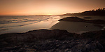Pacific Rim National Park, panoramic twilight scenery in soft red light of the sandy ocean beach during low tide. Green Point, Tofino, Vancouver Island, BC, Canada.