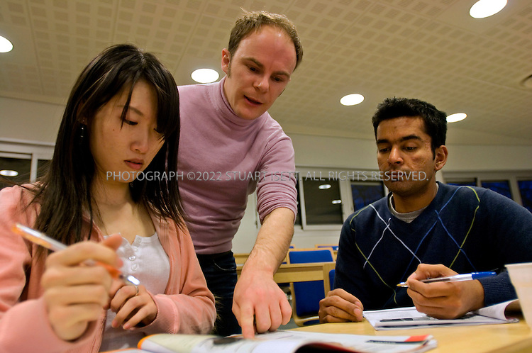 2/24/2006--Jouy en Josas, France..Prof. Alexandre Holle (standing) helping international students in his French language class on the HEC campus. Left to right: Chun-Yin Chang (24, Taiwan) and Eswar Subramanian (27, India). The  majority of students in the MBA program at HEC, a French business school near Versailles, outside of Paris, are now foreign. .Photograph By Stuart Isett.All photographs ©2005 Stuart Isett.All rights reserved.
