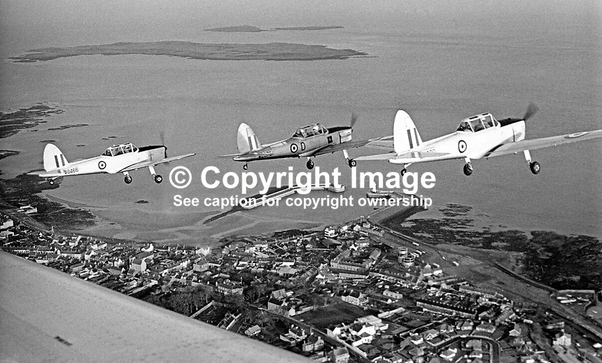 Chipmunks of the University Air Squadron of Queen's University, Belfast, N Ireland, based at the then Sydenham Airfield, now Belfast City George Best Airport fly over the harbour at Donaghadee, Co Down. The Copelands can be seen in the top left of the photograph taken 16th December 1969. Formed 8 January 1941 at Sydenham it was disbanded on 31 July 1996. 196912160262c<br />