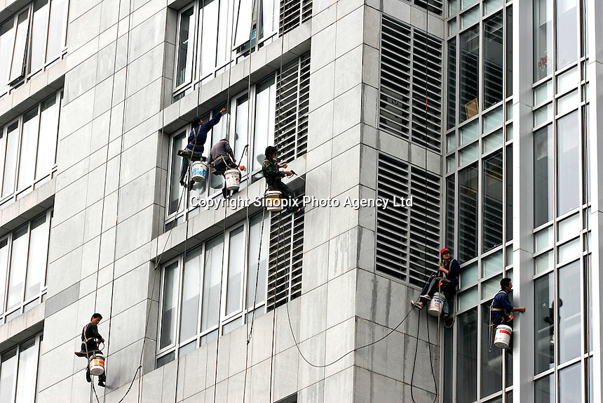 Workers clean curtain wall of a commercial complex in Beijing, China..
