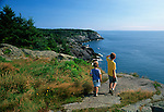 Two boys exploring Monhegan Island's rugged Eastern shore, Monhegan Plantation, Maine, USA