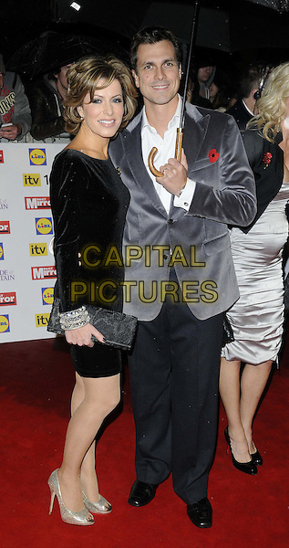 Natasha Kaplinsky & Justin Bower.Pride Of Britain Awards at Grosvenor House, London, England..29th October 2012.full length black dress trousers grey gray suit jacket umbrella married husband wife clutch bag .CAP/CAN.©Can Nguyen/Capital Pictures.