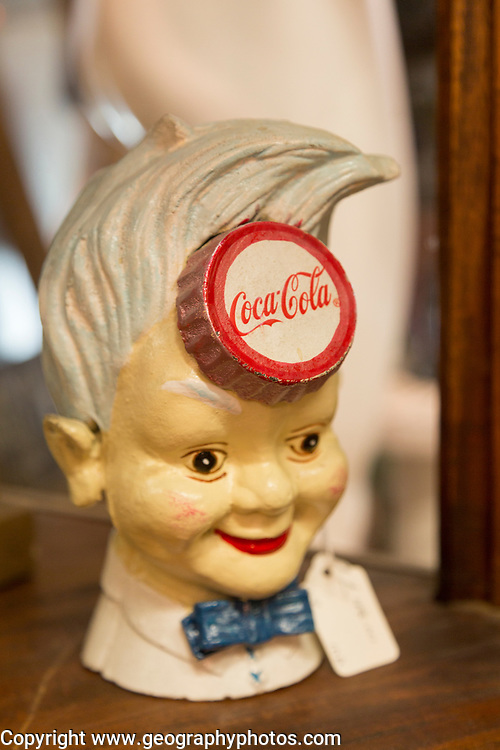 Old vintage Coca Cola advertising sign in form of boy's head inside antiques centre, Marlesford Mill, Suffolk, England, UK
