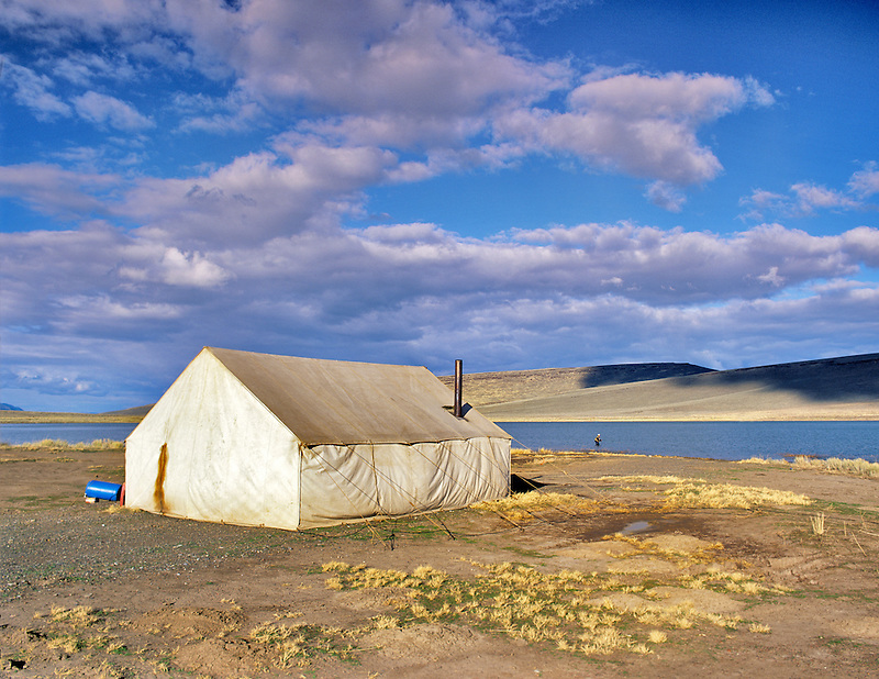 Large canvas tent on shore of Mann Lake with fly fisherman. Oregon.