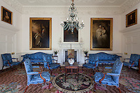 18th century portraits flank the fireplace of the blue drawing room, while the floor is richly covered in an Axminster carpet of the same period