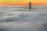 A blanket of fog covers the Golden Gate Bridge at sunrise as seen from the Marin Headlands, California.