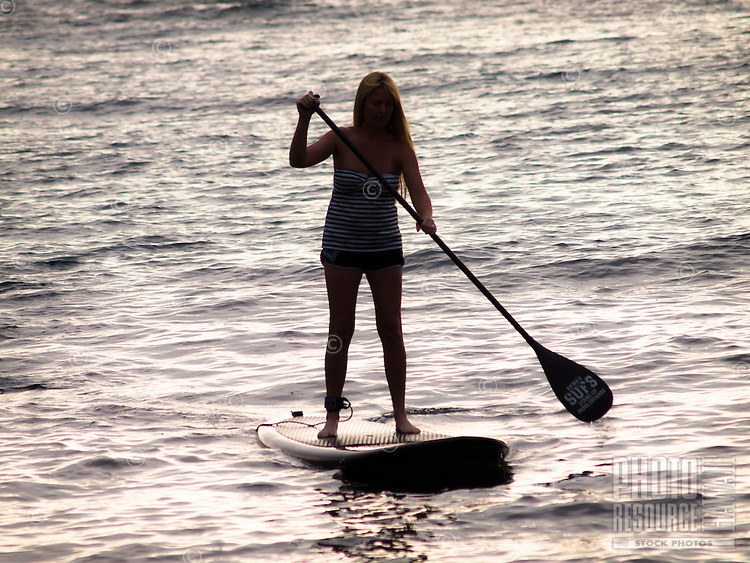 A silhouette of a woman standup paddling at Kahalu'u Beach Park, Kailua-Kona, Big Island.