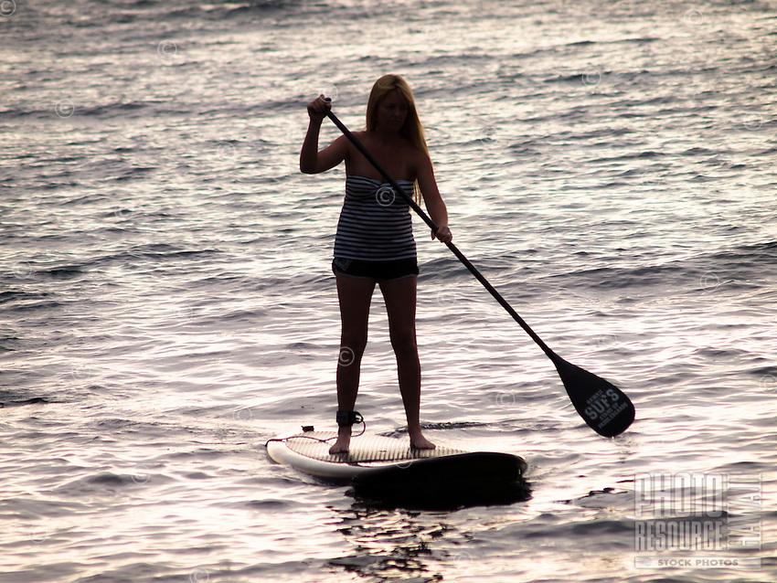 A silhouette of a woman standup paddling at Kahalu'u Beach Park, Kailua-Kona, Big Island.