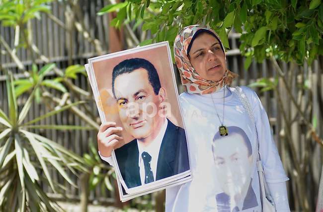 A Supporter of Egypt's former president Hosni Mubarak, holds his pictures after his verdict hearing in a retrial for embezzlement outside the Maadi military hospital, on May 9, 2015 in the capital Cairo. The Egyptian court sentenced Mubarak and his two sons to three years in prison. Photo by Amr Sayed