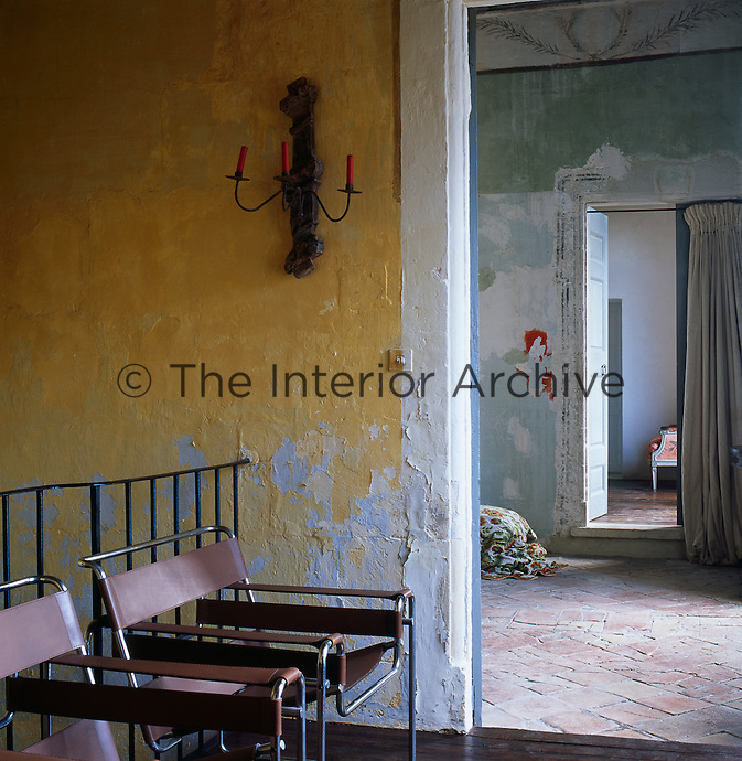 A rustic hall with stone walls painted with natural pigments inspired by the colours of Provence, such as yellow ochre, while being careful to leave the original underlying layers. Two Marcel Breuer Wassily chairs stand in one corner. The distressed finish on the walls gives the rooms a air of faded grandeur.