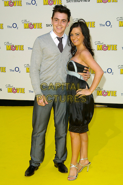 """RAY QUINN & GUEST.""""The Simpsons Movie"""" UK premiere at the Vue O2 Arena cinema, London, England..July 25th, 2007.full length grey gray trousers cardigan black strapless dress hand on hip silver shoes .CAP/CAN.©Can Nguyen/Capital Pictures"""
