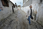 Adham Khalil, a youth activist, walks along a street in the Jabalya refugee camp in the Gaza Strip...