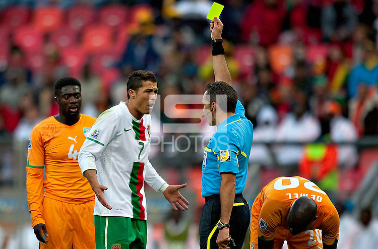 Cristiano Ronaldo of Portugal is booked after clashing with Guy Demel of the Ivory Coast