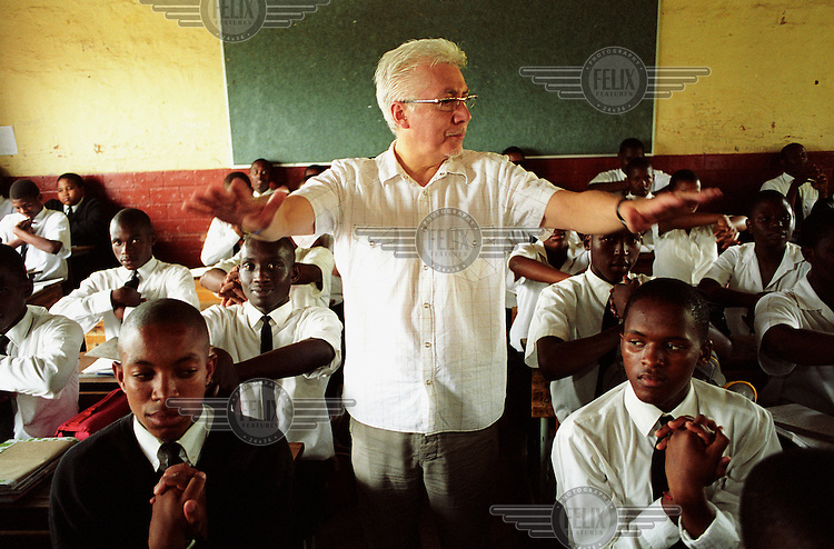 """Alex Wallace, a visiting head teacher, undertakes """"brain gym"""" exercises with students at Zwelibanzi High School in Umlazi Township. .."""