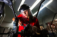 Young female factory worker, aerospace industry, machining and balancing sector, mechanic performing counting and measuring of parts, Brazil.