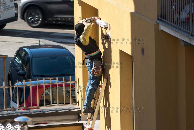 Milano, elettricista al lavoro su una scala all'esterno di una casa --- Milan, electrician at work on a ladder on the outside of a house