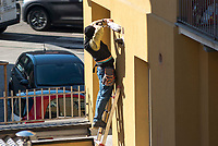 Milano, elettricista al lavoro su una scala all'esterno di una casa --- Milan, electrician at work on a ladder on the outside of a house