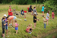 NWA Democrat-Gazette/ANDY SHUPE<br /> A large group of children and their parents fish Thursday, June 15, 2017, at Carter Pond during the annual Elkins Public Library Fishing Derby in Elkins. Prizes were awarded in several categories for children 16 and under before lunch was served.