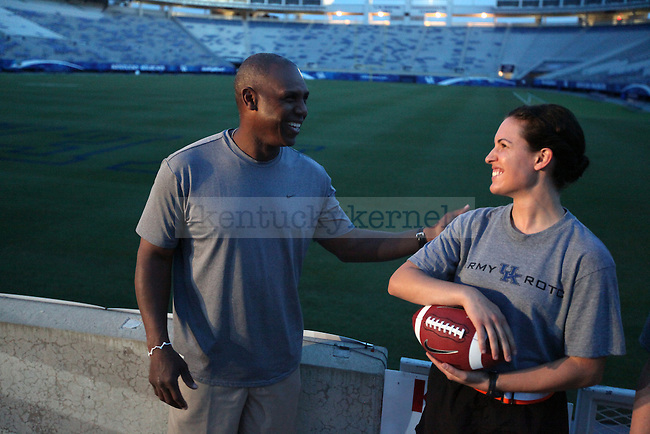 UK football head coach Joker Phillips presents the game ball to nursing senior Jen Graehler for the kick off of football season to UK Army ROTC cadets who will relay the ball to Louisville on Friday, September 4, 2010. Photo by Britney McIntosh | Staff