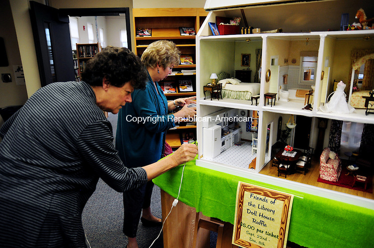 PLYMOUTH, CT, 04 OCT 12-100412AJ02- Nancy Henderson attaches a power cord to a dollhouse she refurbished that is on display at the Terryville Public Library and will be raffled off to raise money for the library on Thursday. Alec Johnson/ Republican-American