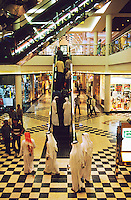 Dubai, United Arab Emirates.  Modern shopping centre/center with traditionally dressed Arab men and people of other races in western dress.
